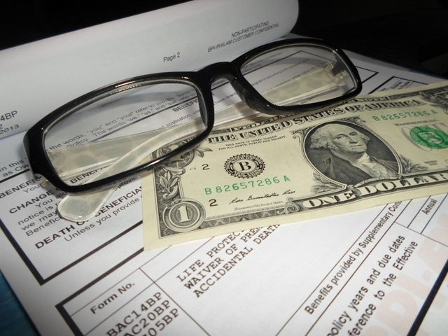 Dollar bills and spectacles on a table